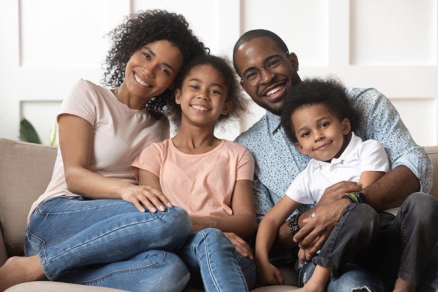 Personal Insurance - Portrait of Happy Family with Children Relaxing on the Couch in Their Living Room