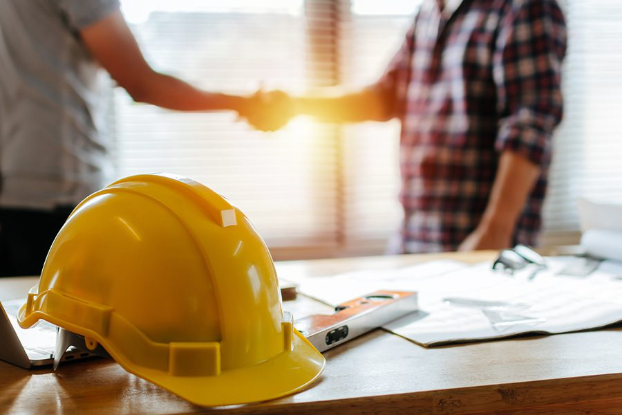 Specialized Business Insurance - Yellow Helmet on Desk with Construction Workers Blurred and Shaking Hands in the Background