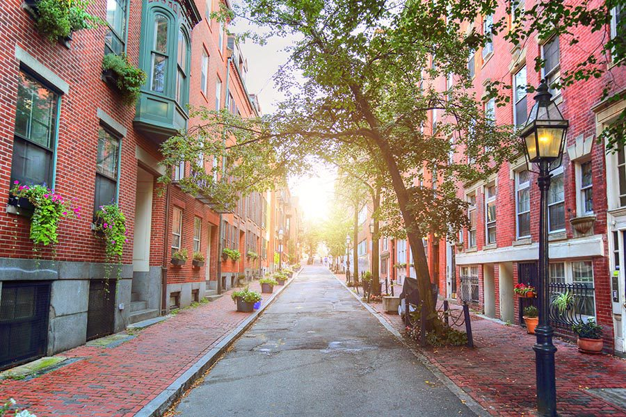 About Our Agency - View Looking Down a Row of Brick Homes in Boston, Massachusetts, the Sun Beaming Down the Center of the Street, Brick Walkways and Street Lamps Lining the Street