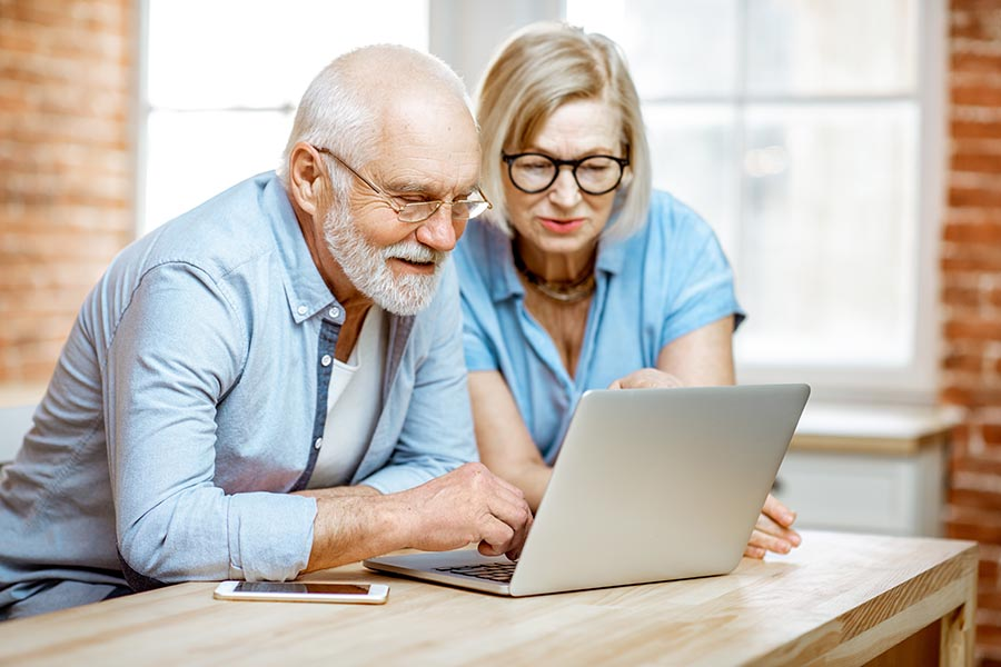 Blog - Senior Couple in Dress Clothes and Glasses Use a Laptop at Their Table in Their Brick Apartment