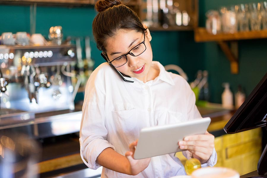 Contact Us - Restaurant Owner Uses a Tablet and Cell Phone Behind the Counter, Wearing Glasses and a White Dress Shirt