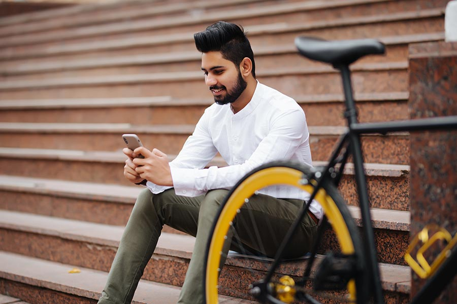 Mobile App - Young, Well-Dressed Man Uses Smartphone Sitting on Public Stairs With His Bike Next to Him