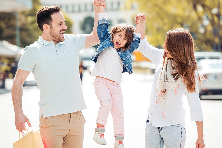 Personal Insurance - Parents Lift Their Young Daughter in the Air as They Walk Through a City on a Sunny Summer Day
