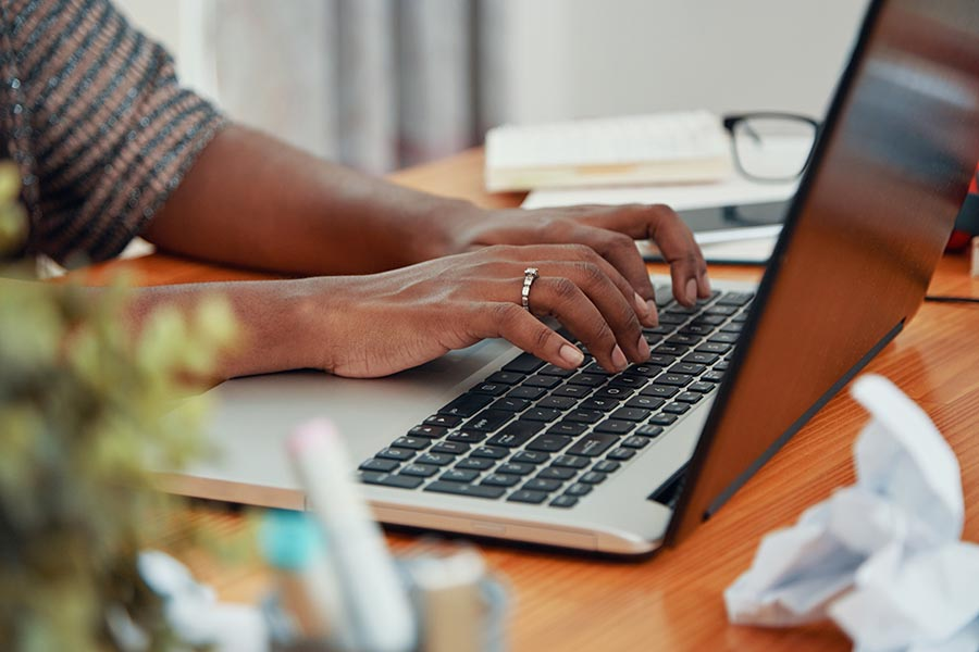 Resources - Woman's Hands Using a Laptop on a Crowded Wooden Desk, Reading Glasses Set to the Side