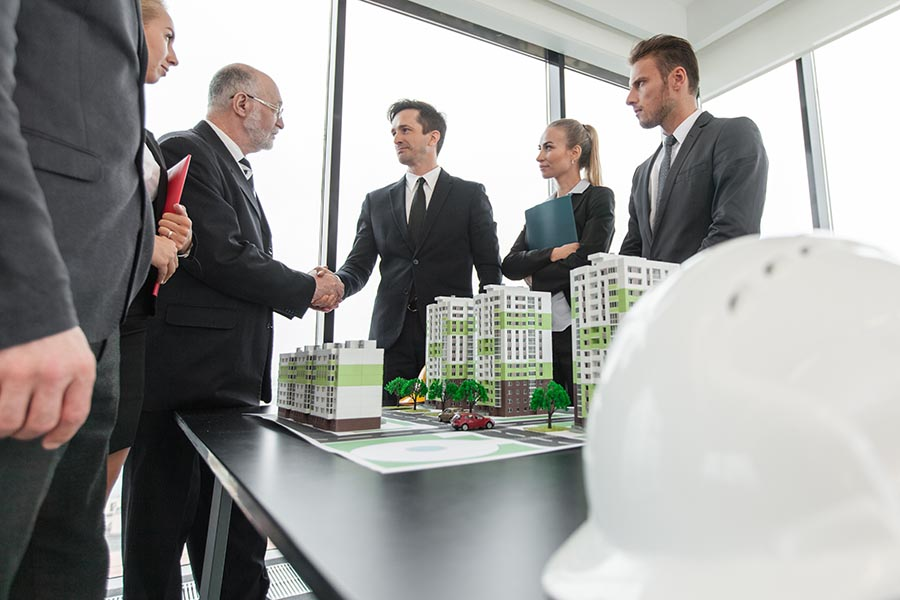 Specialized Business Insurance - Business Associates Shake Hands Over Scale Model of a Planned Condominium Community, a White Hardhat in the Foreground