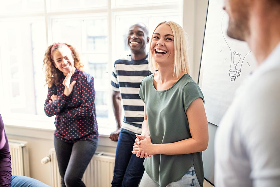 Employee Benefits - Group of Employees Laugh During a Presentation, Sun Coming Through Large Windows, a Brainstorming Board Behind Them