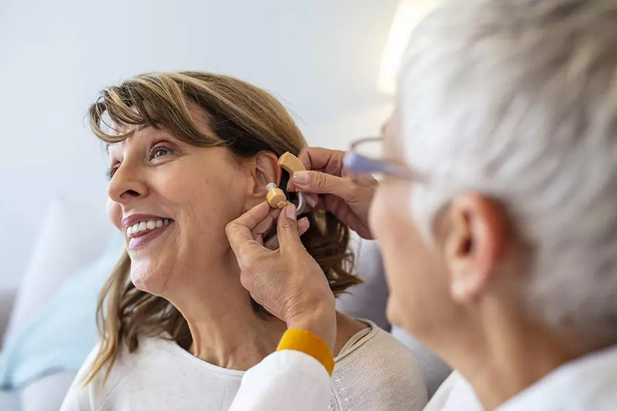 Dental Vision and Hearing Plans - Doctor Adjusting Hearing Aid of a Senior Patient in Her Office
