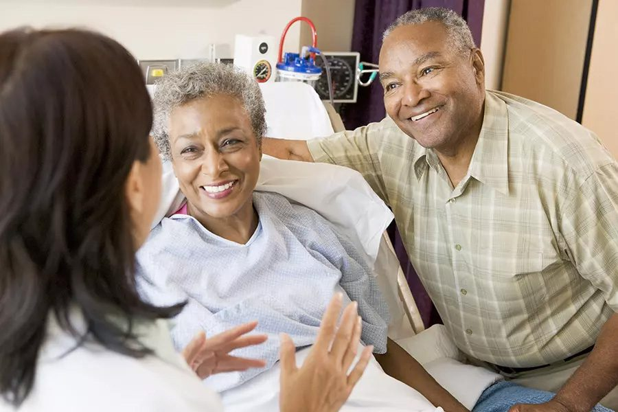 Hospital Indemnity Plans - Doctor with Patient and Her Husband in a Hospital Room
