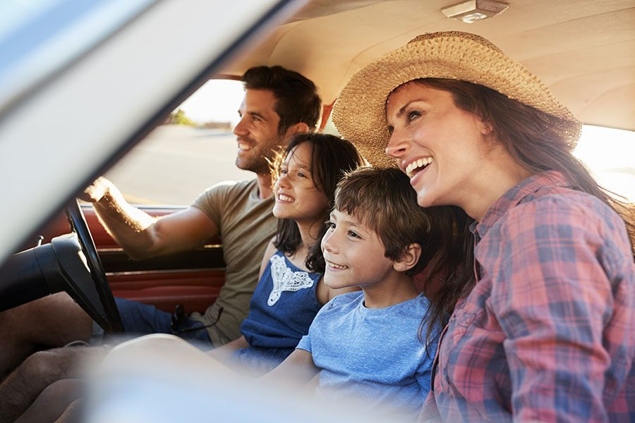About Our Agency - View of Cheerful Family with Two Kids Sitting in a Car During a Summer Road Trip to the Countryside