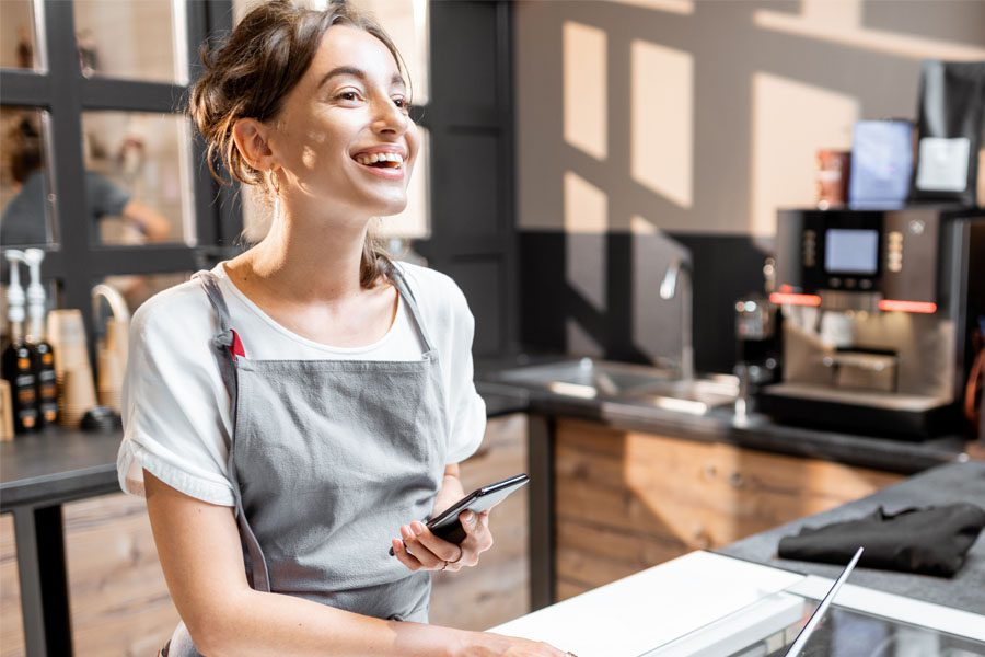 Business Insurance - Portrait of a Cheerful Female Small Business Owner Standing Behind the Counter of Her Ice Cream Shop and Using a Phone and Laptop
