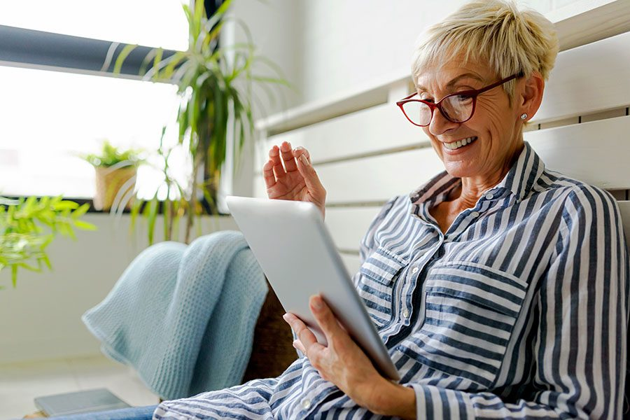 Resources - View of Smiling Mature Woman Sitting on Her Bed Using a Tablet