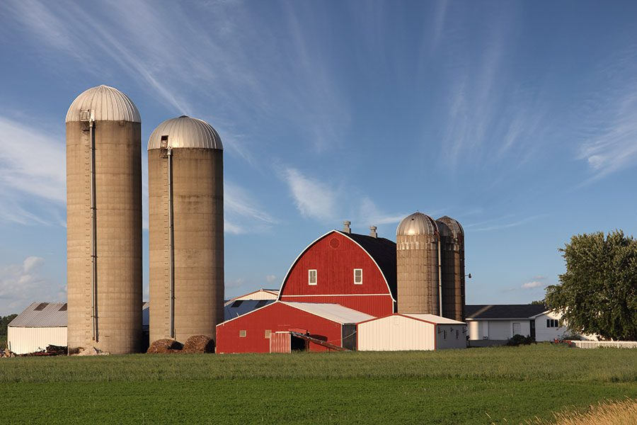 Specialized Business Insurance - View of a Traditional Farm Building with Two Grain Silos in a Rural Setting