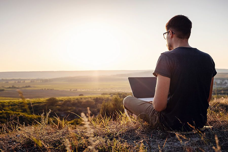 Client Center - Man Sitting on an Open Field in the Countryside Using His Laptop
