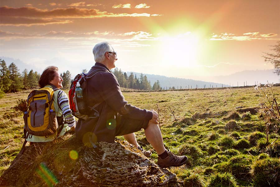 Employee Benefits - Older Couple Sitting on a Rock Watching the Sunset After Hiking