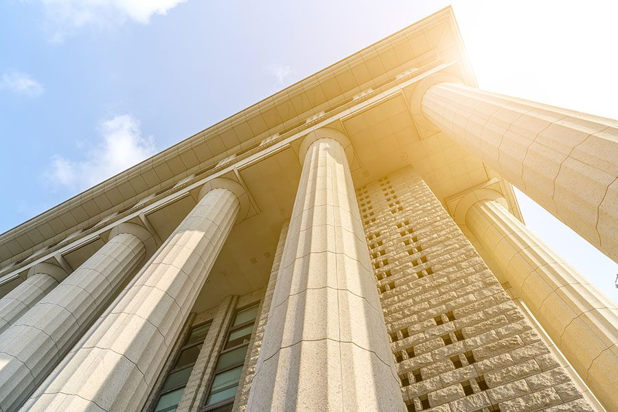 Specialized Business Insurance - Closeup View of Court Building Columns Against Blue Sky