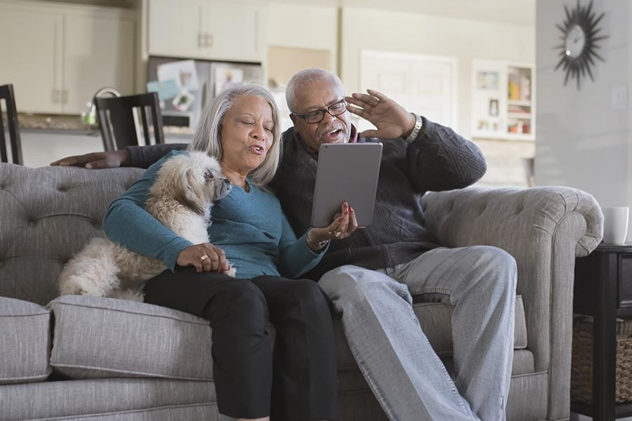 Blog - Senior Couple Reads a Tablet on Their Couch in a Nice Living Room, Small Dog on the Wife's Lap