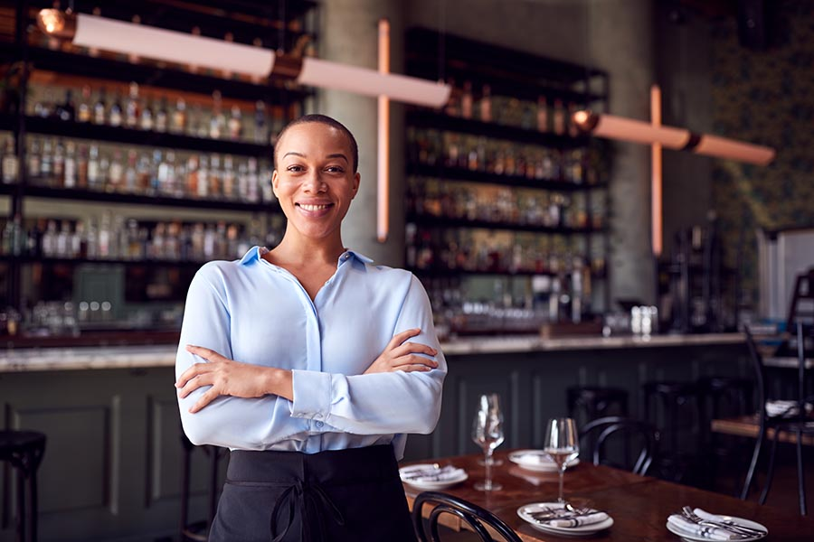 Business Insurance - Restaurant Owner Stands in Front of Her High End Restaurant, Large Stocked Bar and Tables Set for Dinner Service Behind Her