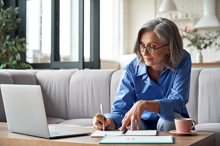 Client Center - Older Businesswoman Makes Notes on Documents at Her Coffee Table, a Laptop Open in Front of Her and Coffee Mug Beside Her
