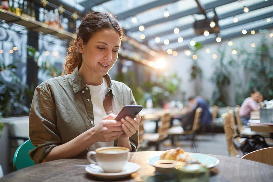 Contact Us - Woman Uses Cell Phone in Cafe, Coffee and a Croissant on the Table, Twinkle Lights Overhead