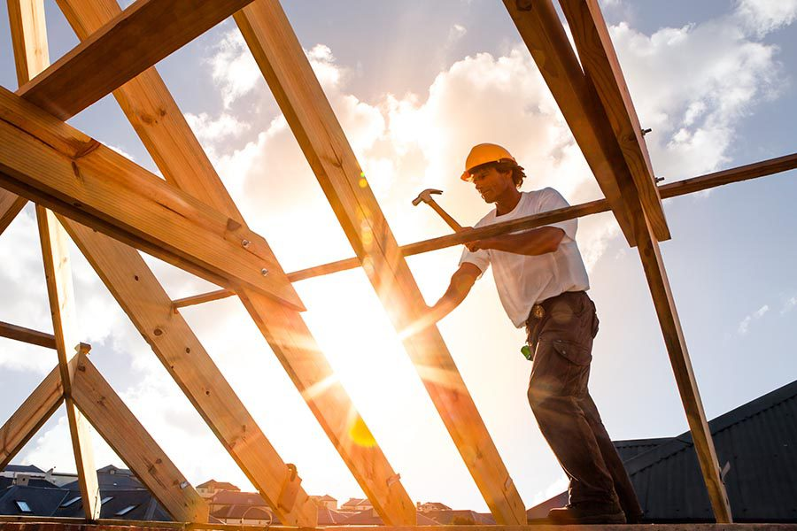 Specialized Business Insurance - Contractor in Hard Hat Erects House Frame on a Sunny Day at Dusk