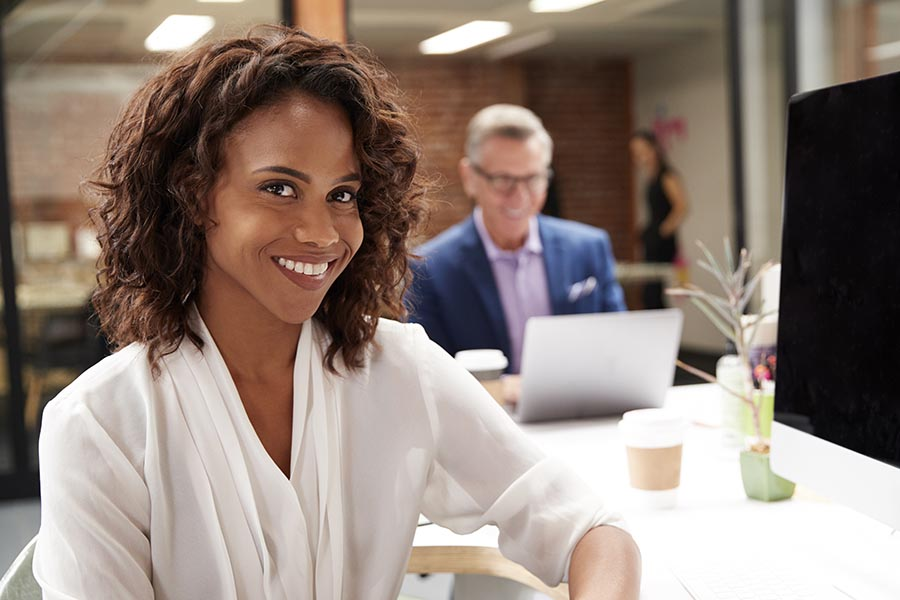 Business Insurance - Boss in White Blouse Smiles Into the Camera From Her White Desk, as Employees Work Behind Her in Their Brick Office Space