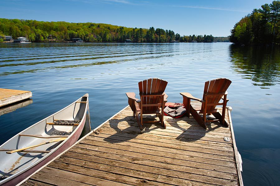 Holden, MA Insurance - Two Wooden Adirondack Chairs Sit on a Wooden Dock on a Small, Calm Lake, a Canoe Floating Nearby