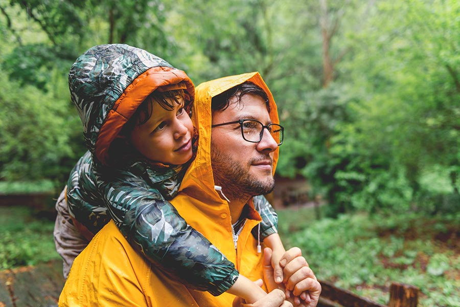 Personal Insurance - Young Son Rides on His Father's Back as They Walk Through a Forrest in the Rain, Both Wearing Rain Coats
