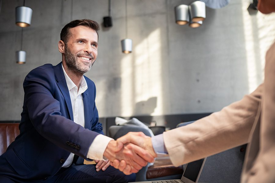 About Our Agency - Business Team Member From Foreshore Insurance Brokers Agency Shaking Hands with Client During a Meeting in a Cafe
