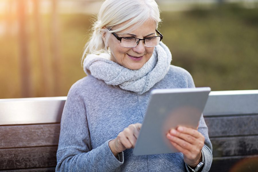 Client Center - Senior Woman Using Digital Tablet Outdoors While Sitting on a Bench