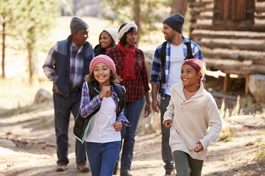 Life and Health Insurance - Multi Generational Family Group On Walk Through Woods In the Fall