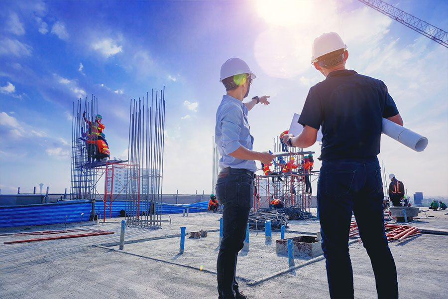 Specialized Commercial Insurance - Business Men Discussing Over Building Designs at a Construction Site on a Sunny Day