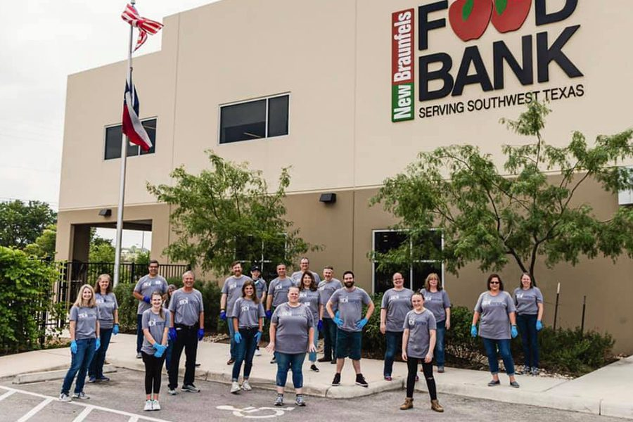 About Our Agency - Portrait of the Team of at Barnard Donegan Insurance Company Posing in Front of a Food Bank After Volunteering Their Time to Give Back to Their Community