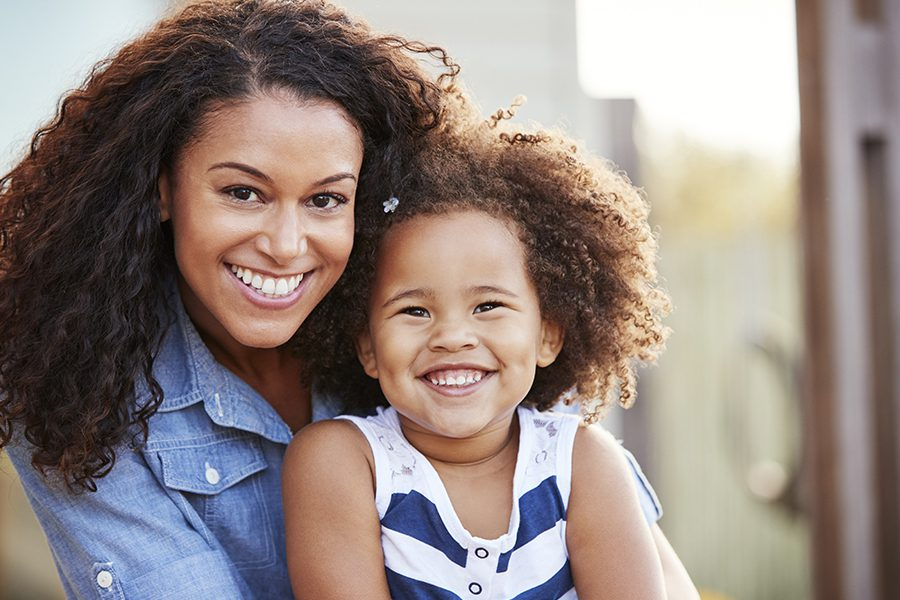 Blog - Closeup Portrait of Mother and Young Daughter Smiling at Camera Outside Their Hom