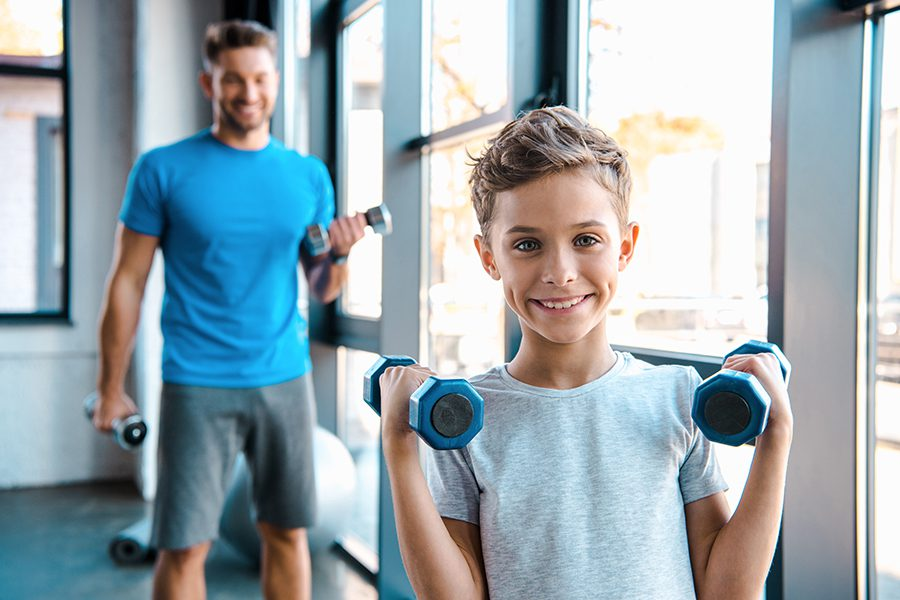 Employee Benefits - Selective Focus of Young Son and His Father with Dumbbells in Exercise Room