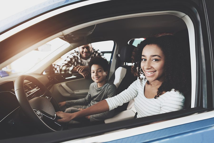 Personal Insurance - Closeup of a Family of Father, Mother and Son Smiling in Their New Car
