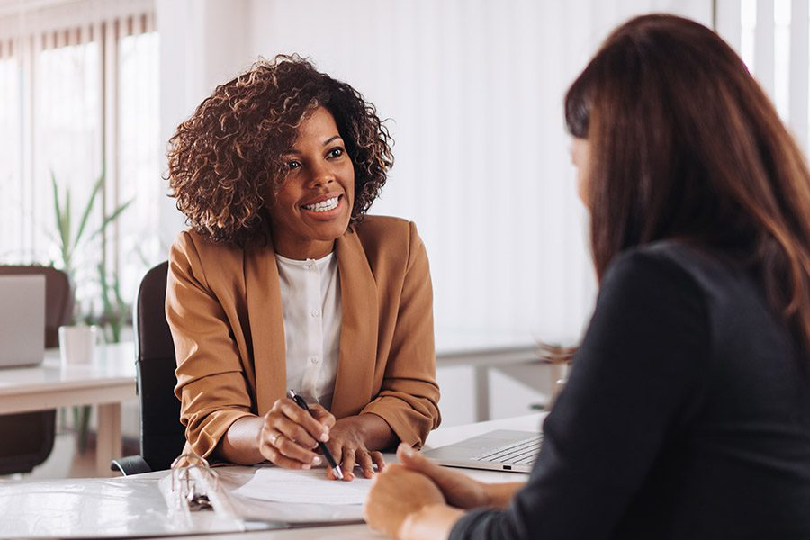 Insurance Agent Insurance - Engaged Insurance Agent Talking to a Potential Client Across the Table