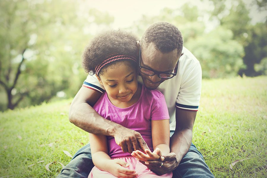 Client Center - Smiling Father Playing with His Daughter at the Park in the Grass on Warm Summer Day