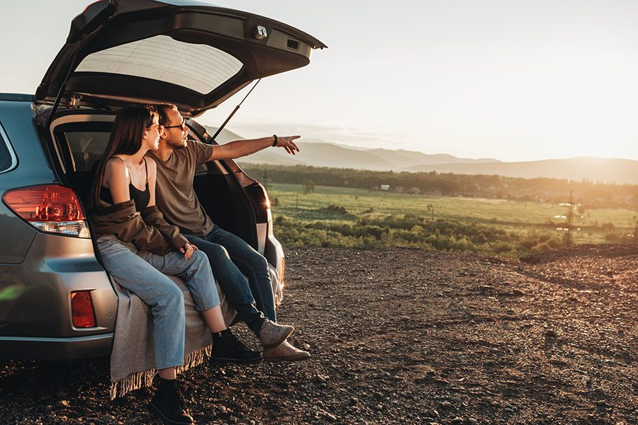 Insurance Quote - Young Couple Sitting in the Trunk of Their Car On a Road Trip Enjoying the Views of the Countryside at Sunset