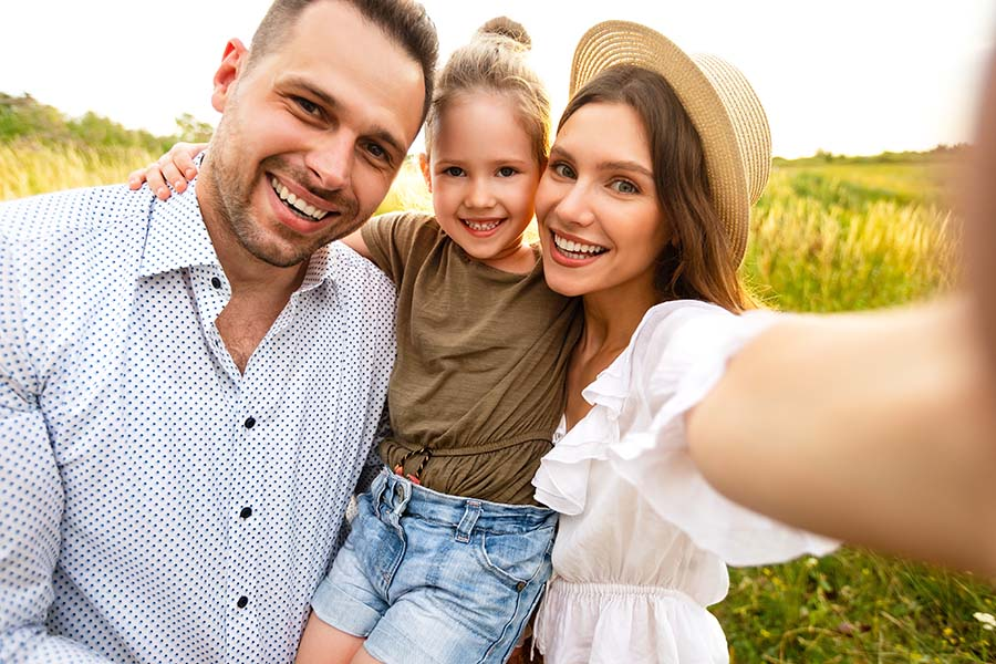 Personal Insurance - Portrait of Joyful Family with Young Daughter Enjoying a Trip to the Countryside During the Summer
