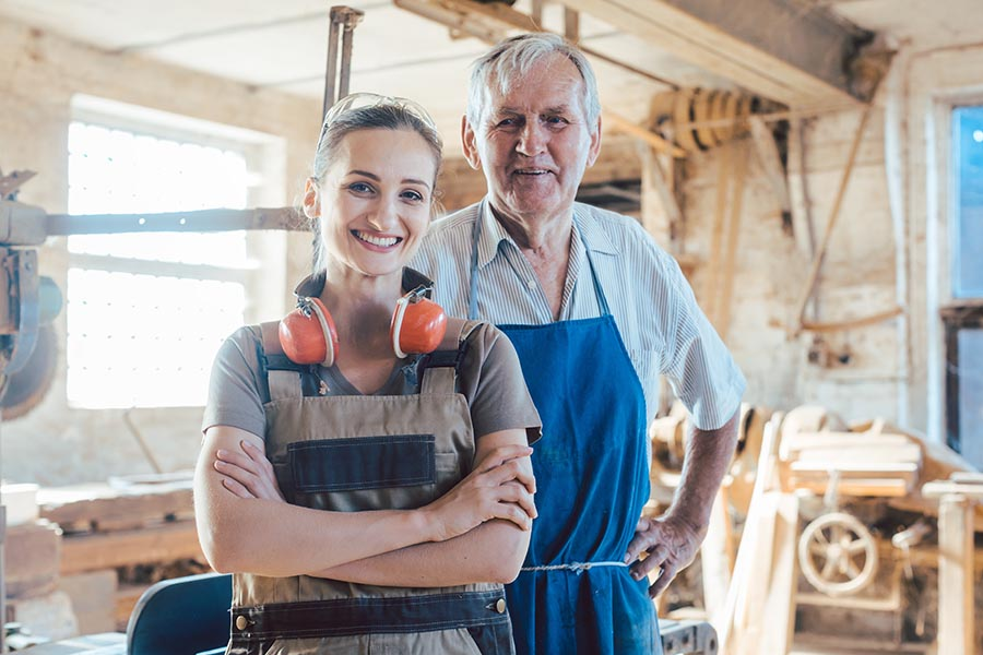 Business Insurance - Father and Daughter Stand in the Workshop of Their Carpentry Business, Wearing Protective Equipment