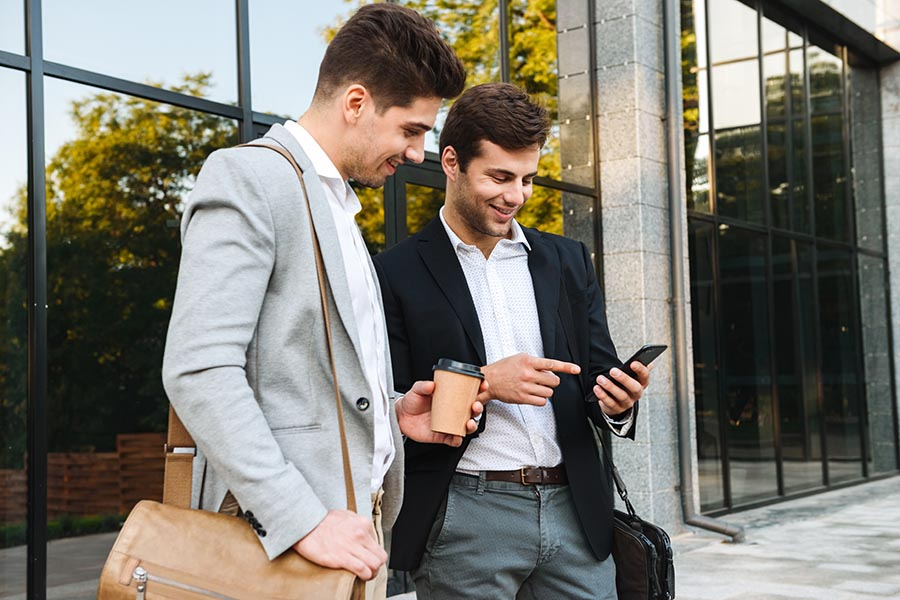 Client Center - Colleagues Grab Coffee Outside Their Office While Collaborating Using a Smartphone
