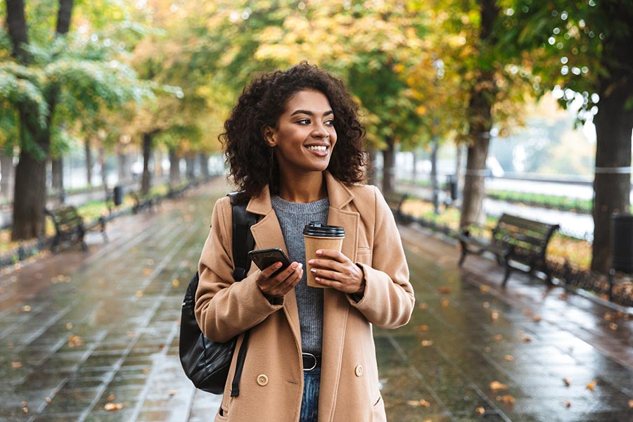 Contact Us - Young Woman Makes a Call While Walking Through a City Park in the Rain Sipping Coffee