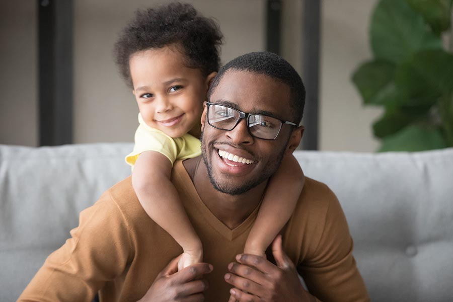 Personal Insurance - Dad Smiles as His Toddler Son Wraps His Arms Over Dad's Shoulders While Perched on Their Couch