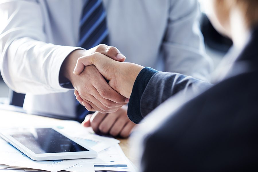 Insurance Companies - Closeup of Business Partners Shaking Hands in the Office
