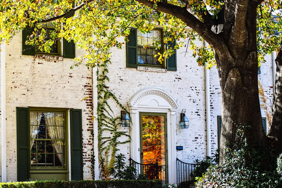 Owasso, OK - Detail of Upscale White Brick House with Reflections of Fall Leaves on the Front Doorin Owasso, Oklahoma