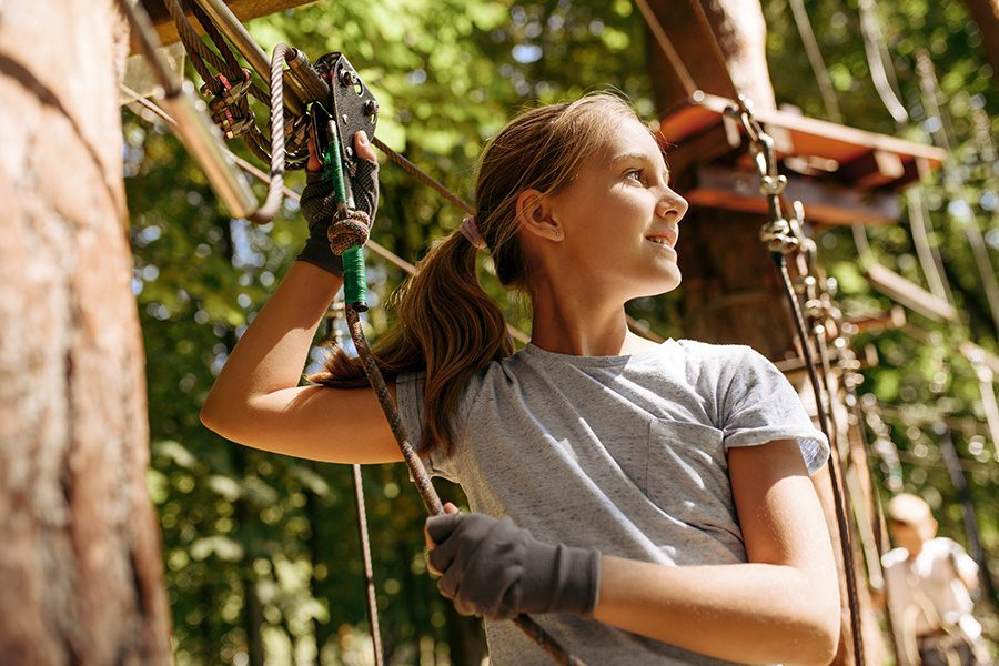 Adventure and Entertainment Insurance - Closeup of Young Girl Climbing Rope and Tree While Using a Harness at an Aerial Adventure Park