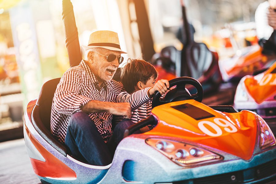 Blog - Grandfather and Grandson Having Fun Together at an Amusement Park