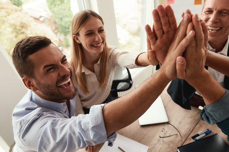 History of Granite - Successful Business Team Giving Each Other High-five and Smiling While Working Together in the Office