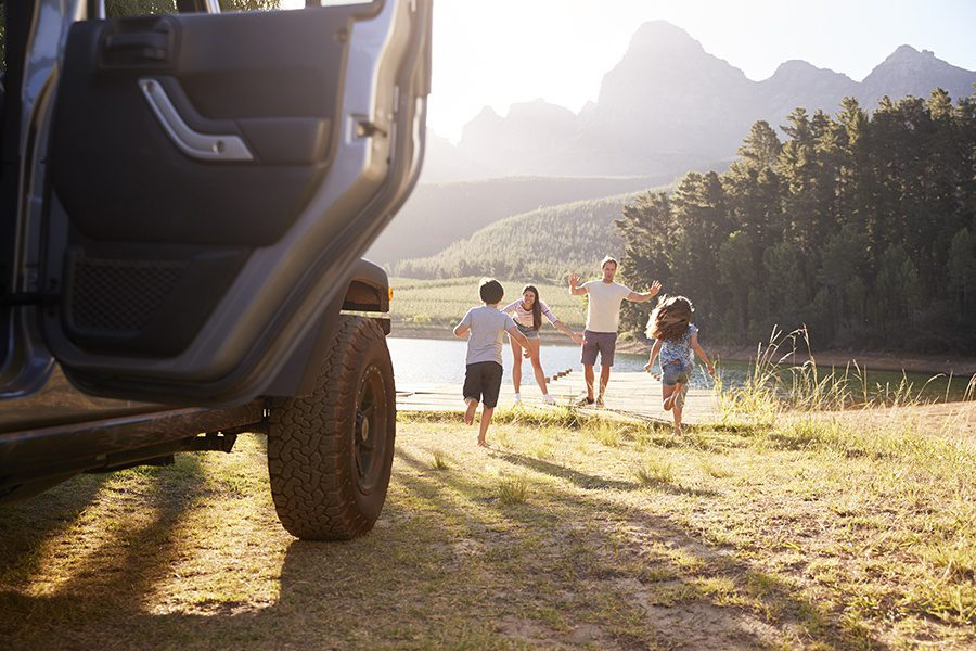 Personal Insurance - Excited Family Leaving Car Door Open While Running Toward Lake On a Road Trip in North Carolina