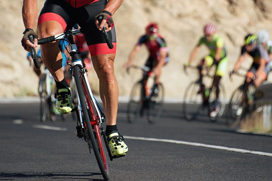 Amateur & Professional Sports Insurance - Closeup Athletes Riding a Race in a Cycling Competition